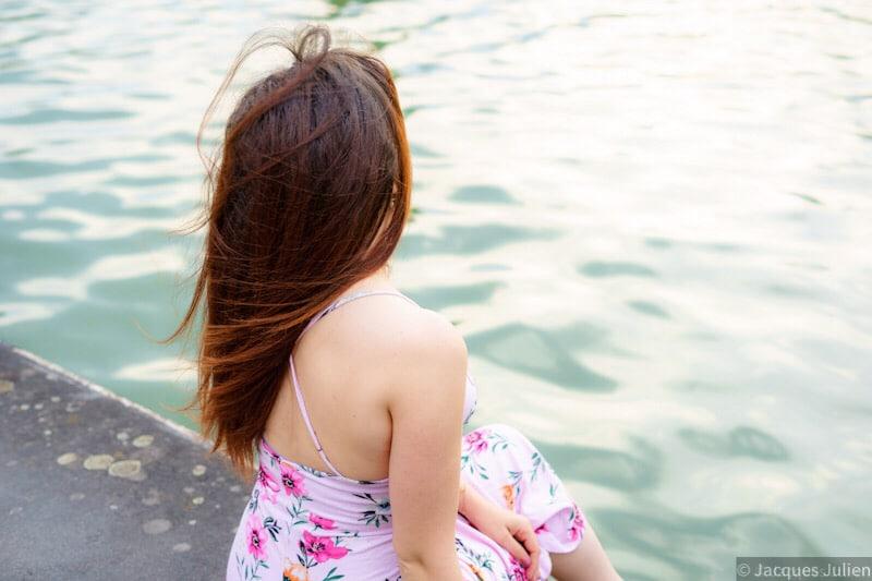 jeune femme de dos au bord de l'eau